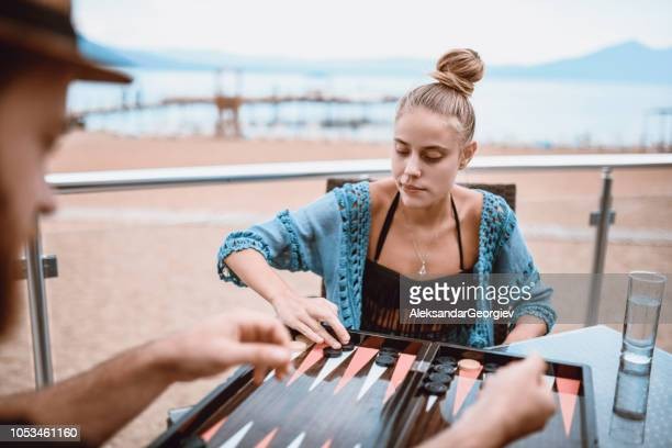 Young Couple Playing Backgammon At The Beach