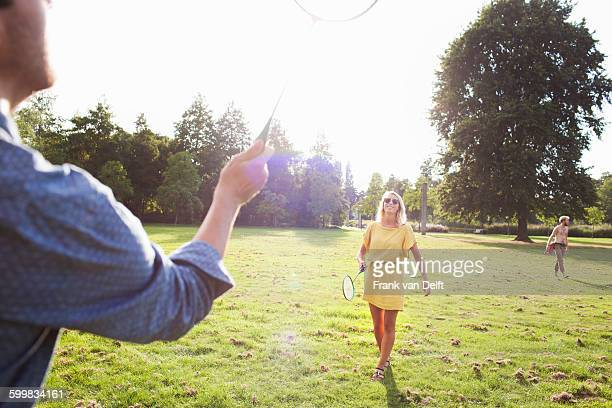 young couple playing badminton in sunlit park - badminton sport stock photos and pictures