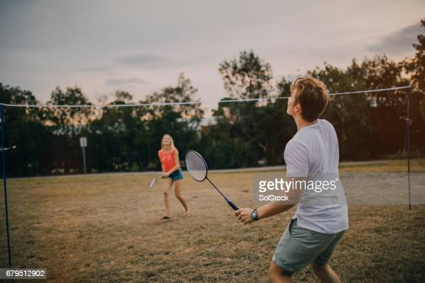 young couple playing badminton in the park - badminton stock photos and pictures