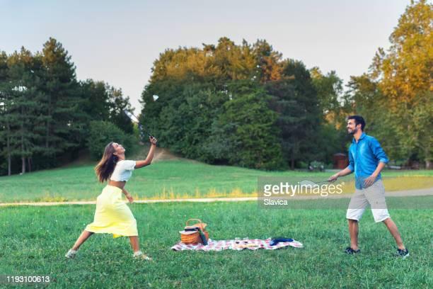 草原でバドミントンをする若いカップル - スポーツ バドミントン ストックフォトと画像