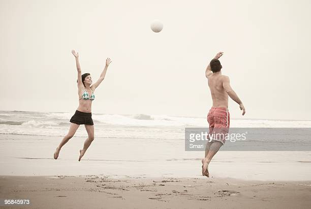 Young couple playing beach volleyball.