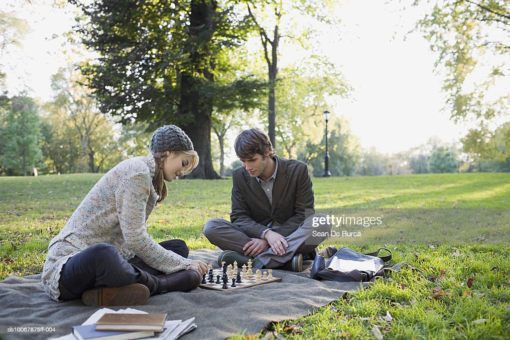 Young couple playing chess in park : Stock Photo