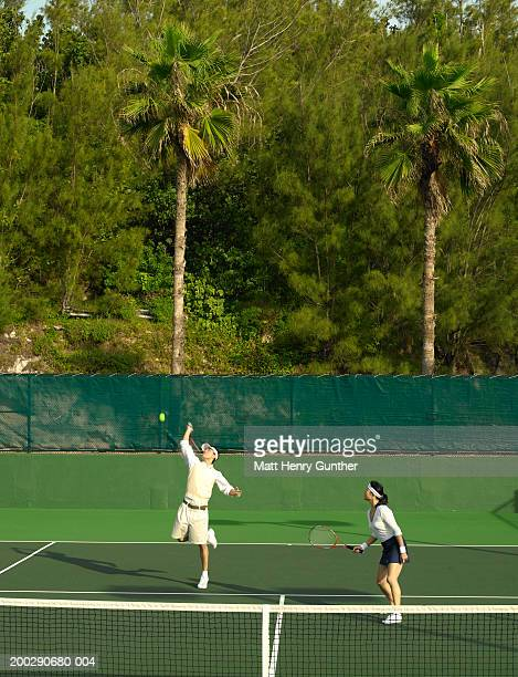 Young couple playing doubles tennis, man serving (blurred motion)