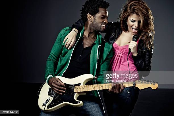 young couple playing electric guitar and singing - duet stock pictures, royalty-free photos & images