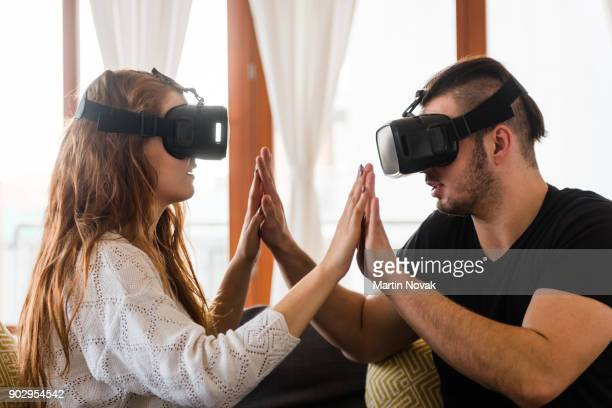 Young couple playing game with new trends technology