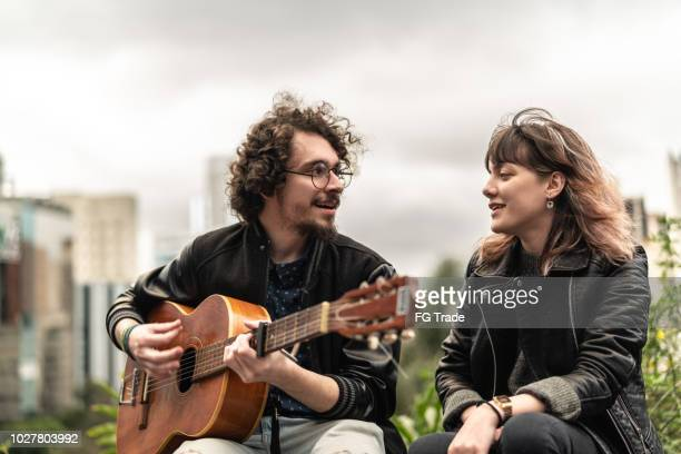 Young Couple Playing Guitar at City