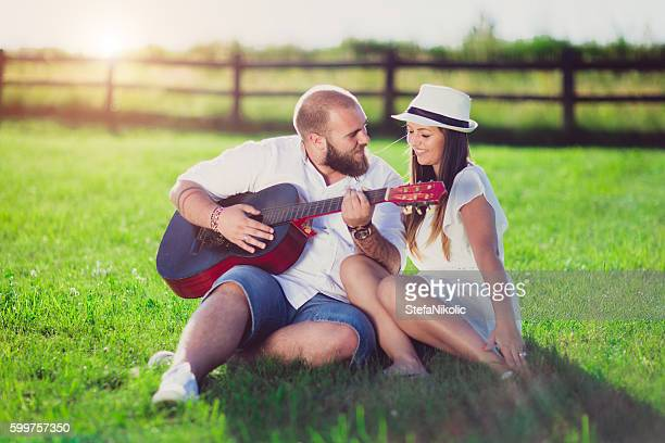 Young couple  playing guitar outdoor