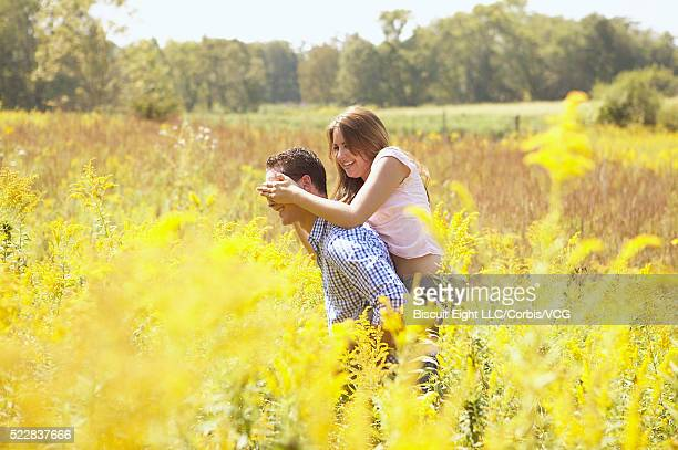 Young couple playing in sunny field