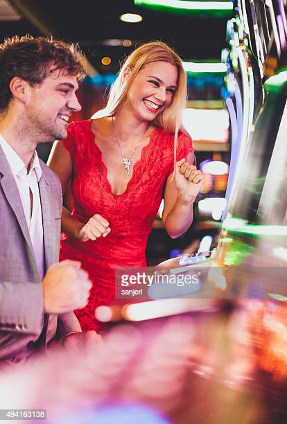 young couple playing slot machines at the casino - casino stock pictures, royalty-free photos & images
