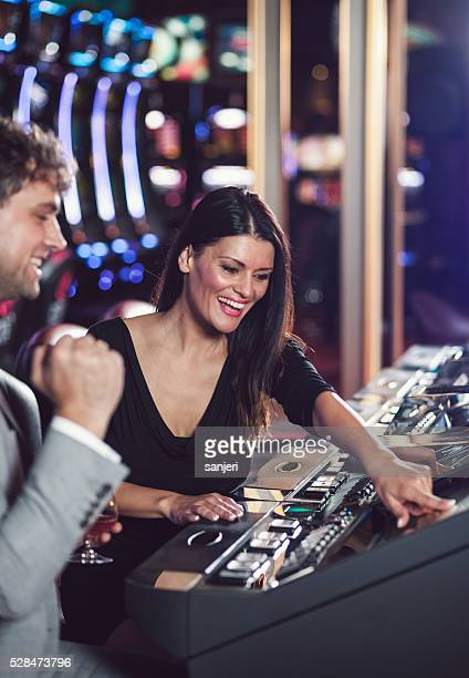 Young couple playing slot machines at the Casino