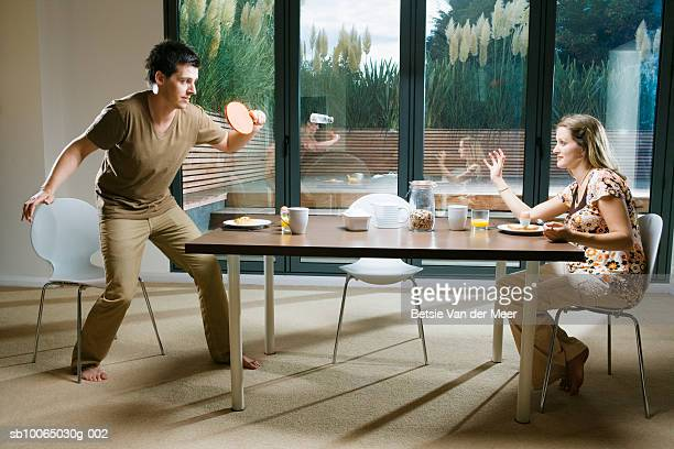 Young couple playing table tennis at dining table, smiling, side view