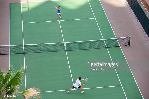 Young couple playing tennis in the court of a tourist resort