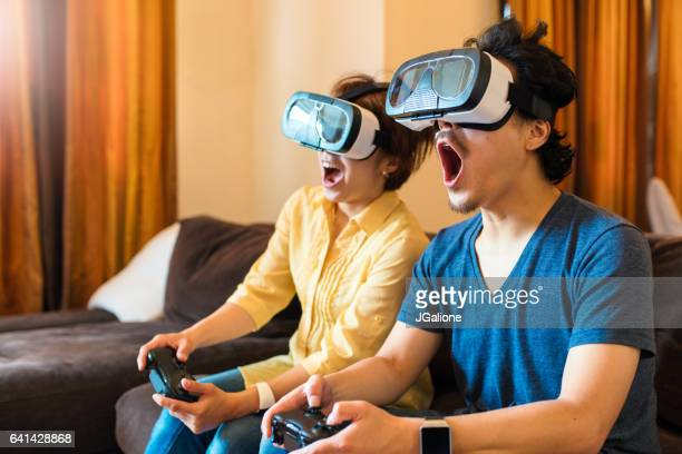 young couple playing virtual reality games together - jgalione stock pictures, royalty-free photos & images