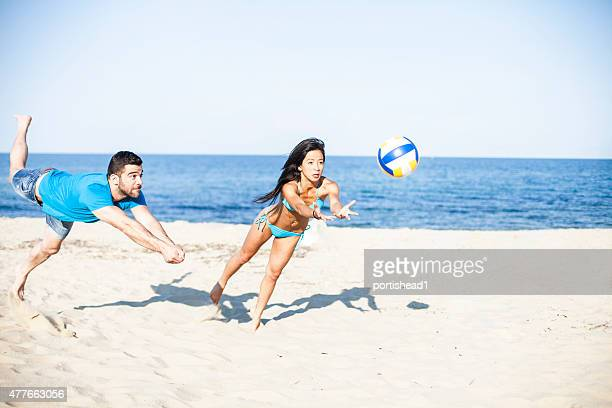 Young couple  playing volleyball on the beach