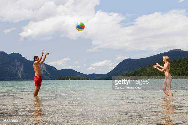 A young couple playing with a beach ball