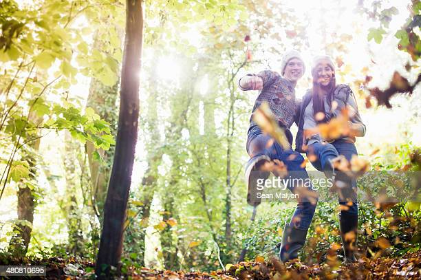 young couple playing with autumn leaves in forest - kicking stock pictures, royalty-free photos & images