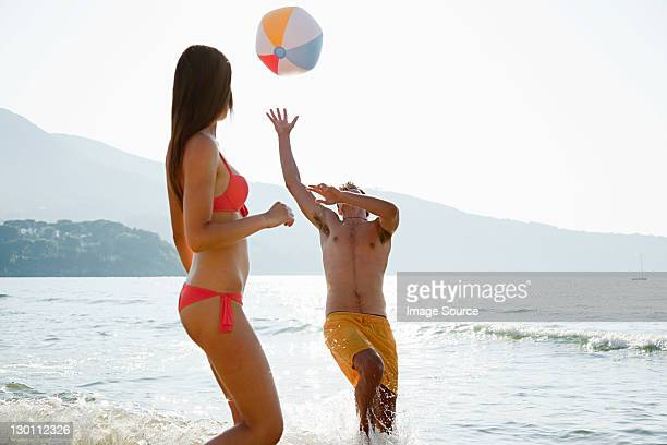 Young couple playing with beach ball on beach