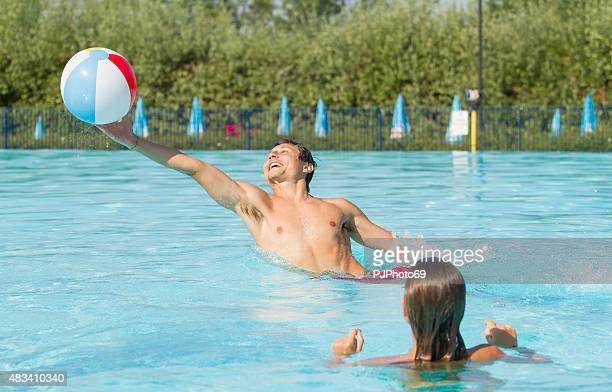 若いカップルが、ビーチボールをプール - pjphoto69 ストックフォトと画像