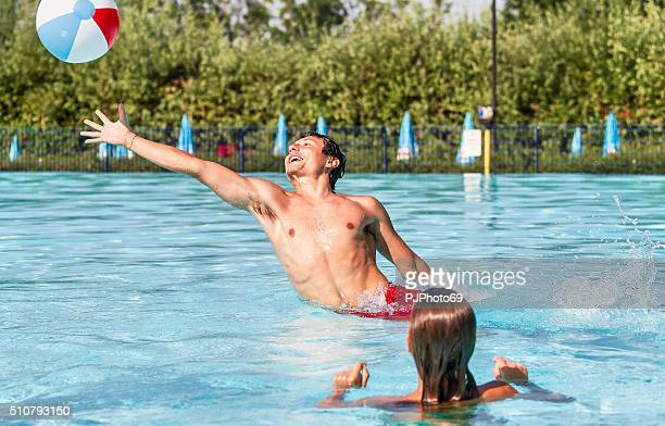 Young couple playing with beach ball on swimming pool