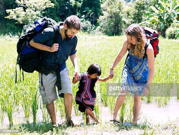 young couple playing with child (4-5), chiang mai, thailand - hugh sitton bildbanksfoton och bilder