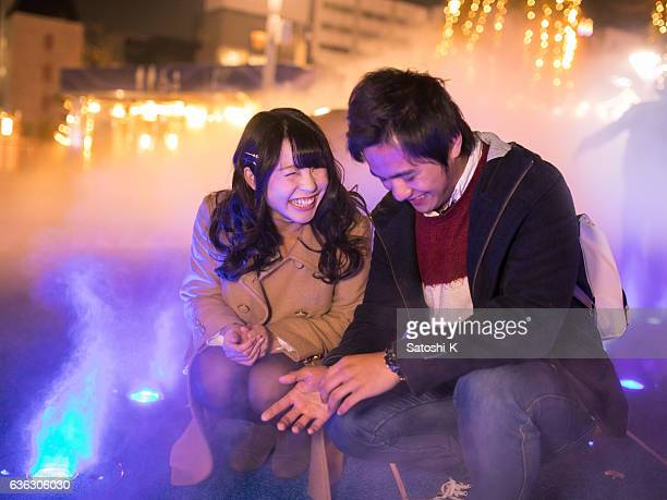 Young couple playing with fog at Christmas night