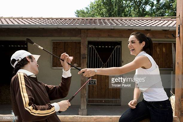 young couple playing with riding crops - riding crop stock photos and pictures
