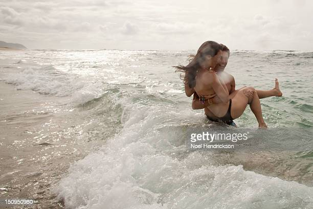 A young couple plays in the ocean together