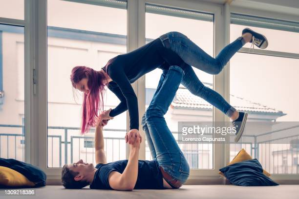 young couple plays on the floor of their new home. - mortgage stock pictures, royalty-free photos & images