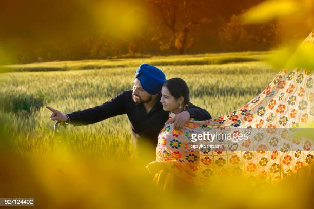 young couple pointing and looking out - punjab india stock pictures, royalty-free photos & images
