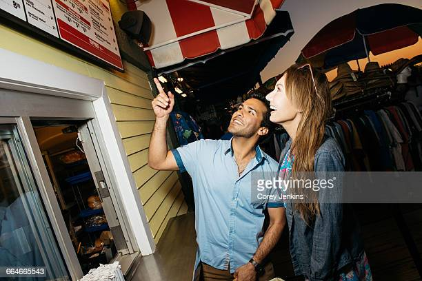 Young couple pointing at hotdog menu in amusement park at night, Santa Monica, California, USA