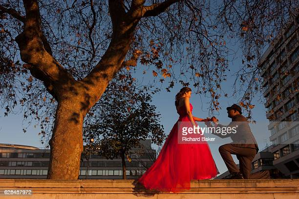 A young couple pose for wedding photos on the Southbank on 29th November 2016 in London England London like many world cities the wedding photo...