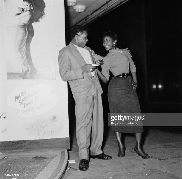 A young couple pose outside the 'Club Americana' a Saturday night jazz club open from midnight until 7 am London 25th November 1955