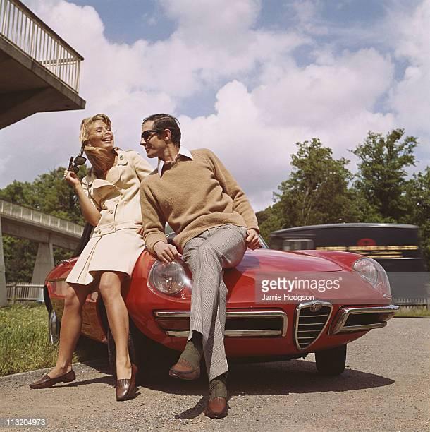 A young couple pose with their Alfa Romeo Spider circa 1970