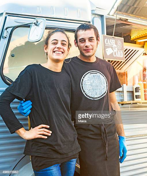 Young couple posing by their food truck