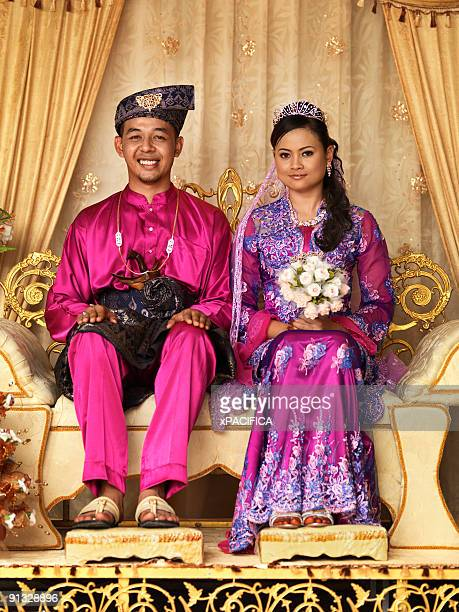 A young couple posing for their wedding photo.