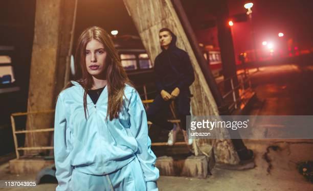 joven pareja posando en una estación de ferrocarril - chándal fotografías e imágenes de stock