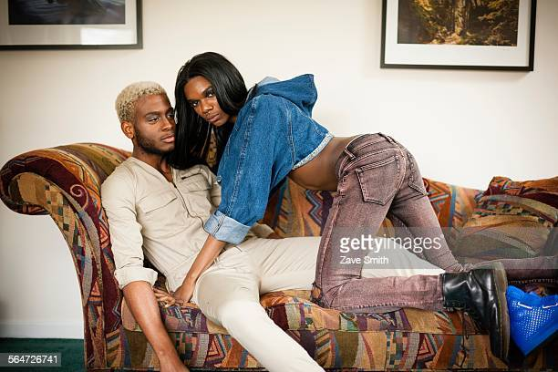 young couple posing on sofa - transgender man stock photos and pictures
