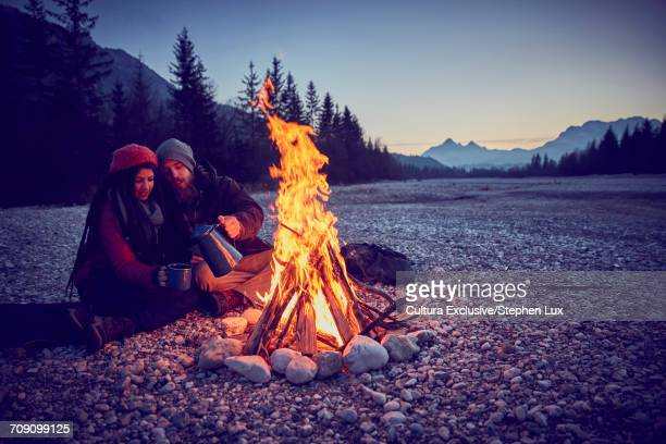 Young couple pouring coffee by campfire at River Isar, Karwendel Mountains, Bavaria, Germany