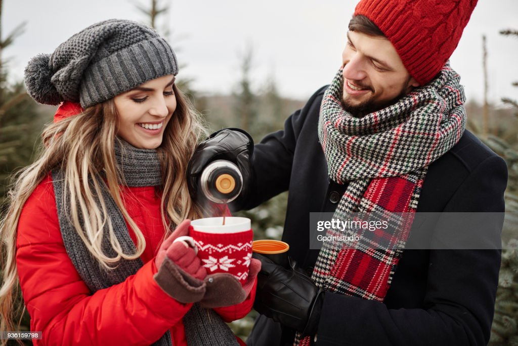 Young couple pouring coffee while shopping for christmas tree from forest : Stock Photo