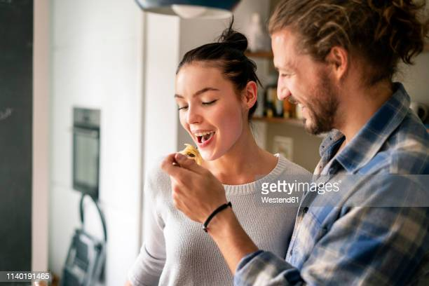 young couple preparing food together, tasting spaghetti - kochen stock-fotos und bilder