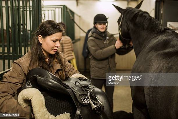 young couple preparing horse in stable - riding stock pictures, royalty-free photos & images