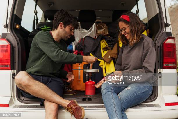 young couple preparing sausages on a camping stove - heterosexual couple stock pictures, royalty-free photos & images