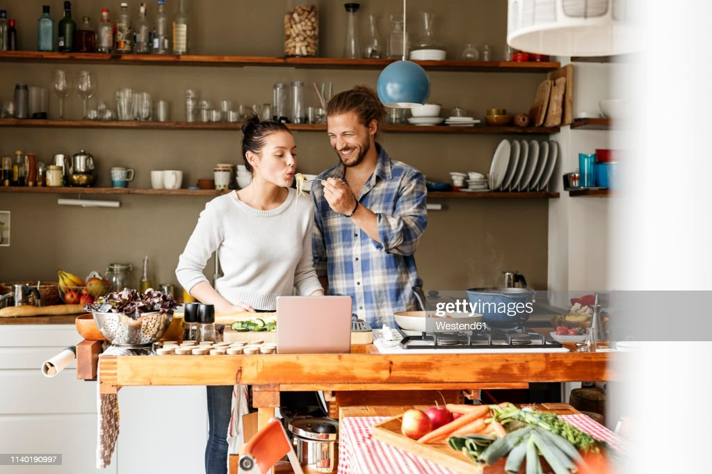 Young couple preparing spaghetti together, using online recipe : Photo