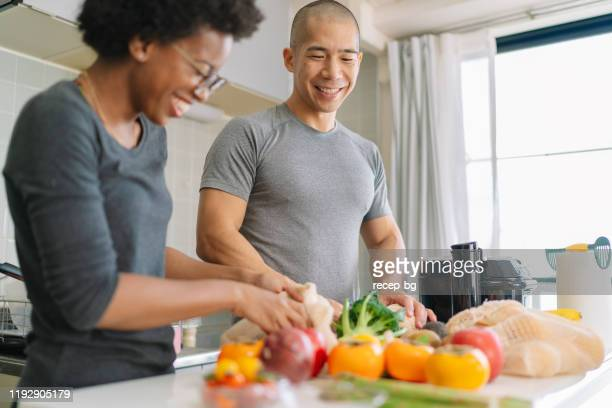 young couple preparing vegan food at home - healthy eating stock pictures, royalty-free photos & images