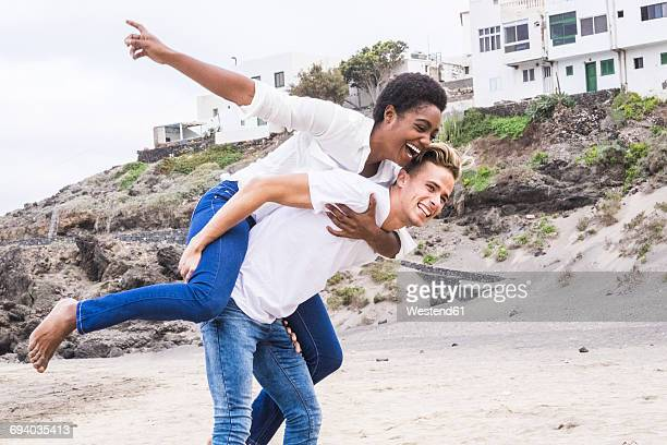 Young couple pretending to fly on a beach