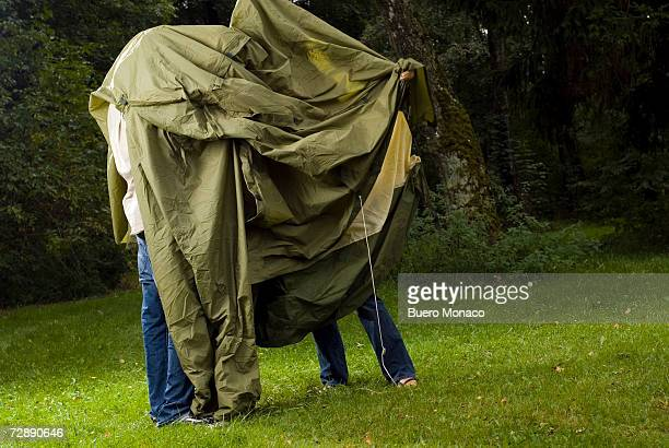 young couple putting up tent on clearing - putting stock photos and pictures