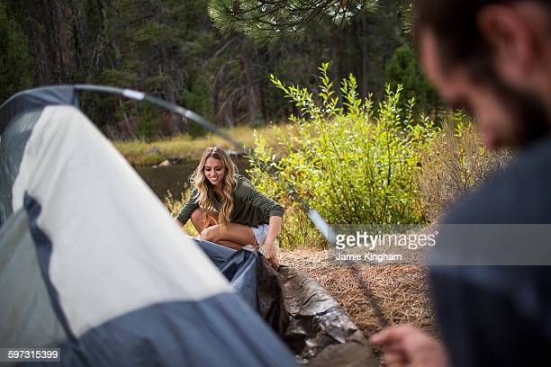 Young couple putting up tent on riverside, Lake Tahoe, Nevada, USA