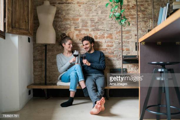 Young couple raising a toast on kitchen bench