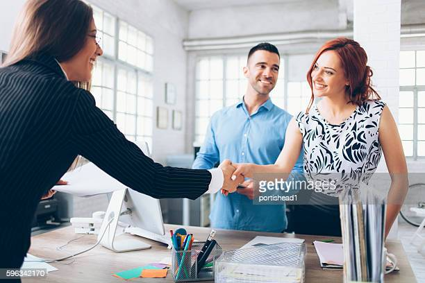 Young couple reaching an agreement with agent