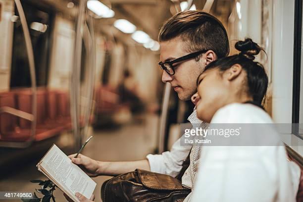 Junges Paar lesen ein Buch auf der U-Bahn